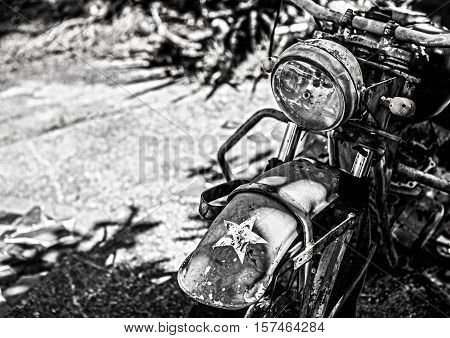 Ancient military motorcycle in the rainforest. Black-white photo.