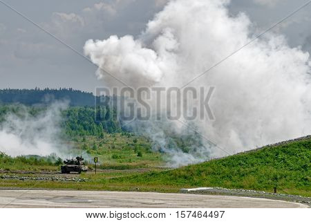 Nizhniy Tagil, Russia - July 12. 2008: T80 tank hides under smoke screen, Display of fighting opportunities of arms and military equipment. RAE exhibition