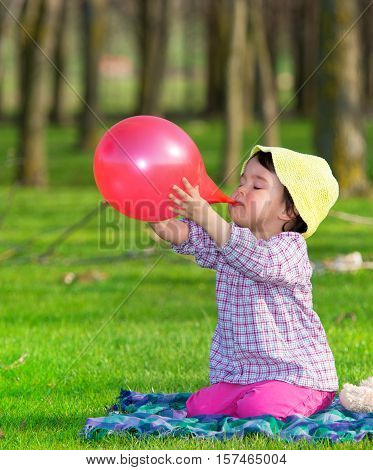 Little girl  inflating red balloon outdoors in summer