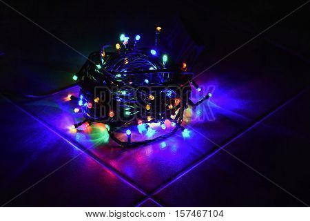 Christmas Lights On Black Background With Copy Space. Colored Reflecting Surface.