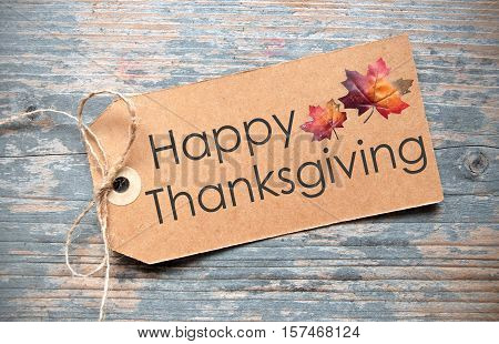 Happy thanksgiving handwritten on a label with autumn leaves