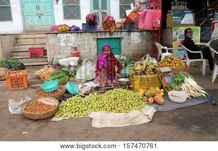 PUSHKAR, INDIA - FEBRUARY 18: Woman selling fruit and veg at a street market in Pushkar, Rajasthan, India, on February 18, 2016.