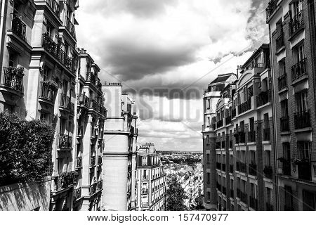 Black-white photo of view from Montmartre to summer Paris and beautiful cloudy sky. Paris France.