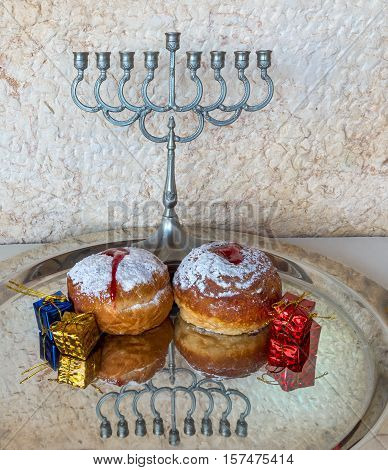 Festive sweet donuts and menorah are traditional symbols of Hanukkah holiday. Selective focus