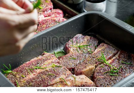 Raw Beef Steak with spices and seasoning preparation for grill.