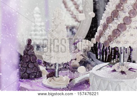 Beautiful set of three handmade white and purple croquembouche wedding cakes made from meringue and macarons standing on small dessert table reflecting in mirror