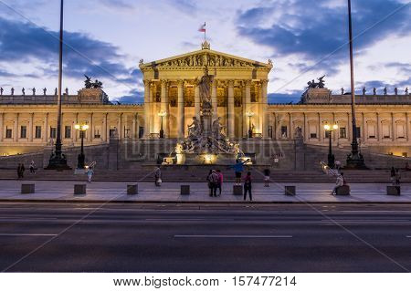VIENNA AUSTRIA - 23RD AUGUST 2016: The outside of the Austrian Parliament at night. People can be seen outside