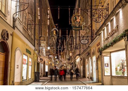 SALBURG AUSTRIA - 11TH DECEMBER 2015: A view along Getreidegasse in Salzburg at night during the Christmas season. People shops and buildings can be seen.