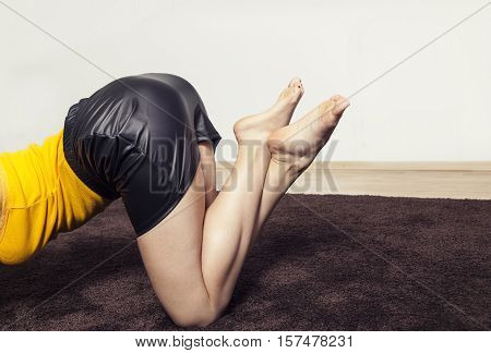 Sexy girl on her knees on a carpet close up of the lower body with crossed legs barefeet in black leather skirt and yellow top side view