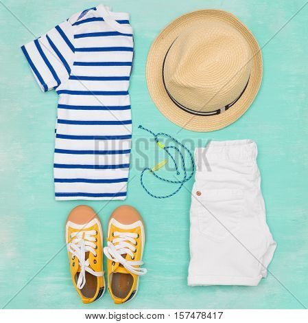 Child's striped t-shirt demin shorts accessories yellow shoes and straw hat on turquoise wooden background. Top view. Flat lay. Kid's summer clothes collage