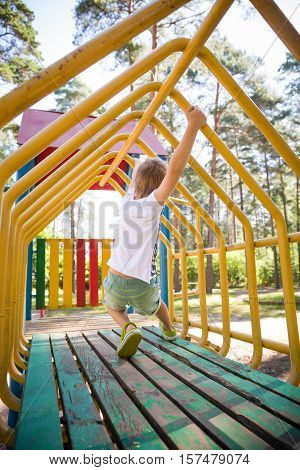 Portrait of cute kid boy playing on the climbing frame. Young boy climbing on playground during summer. Child enjoys climbing through a tunnel in a children's playground outdoors.