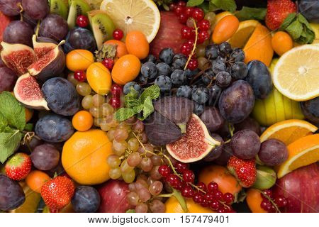 Top view on mixture of different fruit and berries: lemons figs grapes tangerines apples strawberry plums red current oranges. Healthy food concept