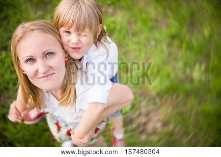 Happy adorable kid boy sitting on his mom's shoulders and laughing. Young blond mother with blond child. Summer vacations. Outdoor. Top view. Happy family.