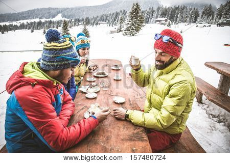Group of friends talking and having fun in a outdoor restaurant on winter holidays - Snowboarders drinking hot coffee in a bar