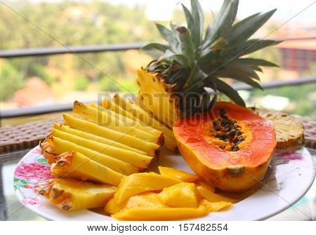 tropical fruit pineapple mango corambola papaya on the plate served on palm tree for dietary light breakfast