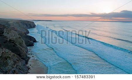 Aerial from rocks and ocean at Praia Vale Figueiras in Portugal at twilight