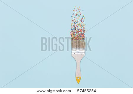 Colorful confetti splashing from paintbrush on blue background. Party celebration Christmas concept.