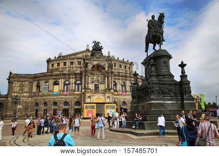DRESDEN GERMANY - AUGUST 13 2016: Tourists walk and visit on Semperoper opera (Staatskapelle Dresden) at Theaterplatz building was designed by Gottfried Semper in Dresden Germany on August 13 2016.