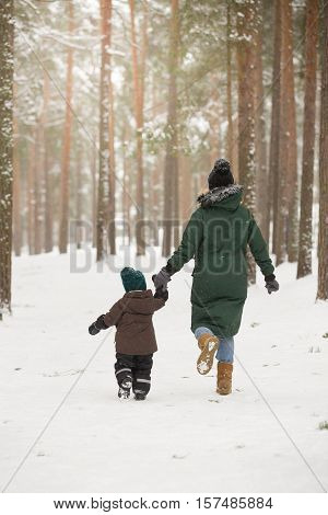 Mother and little toddler boy walking in the winter forest and having fun with snow. Family enjoying winter. Child and woman running outdoors. Winter Christmas and lifestyle concept.