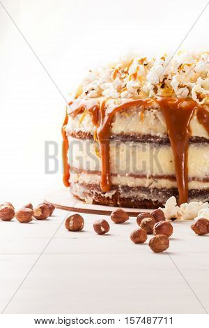 Homemade cake with hazelnuts and salty caramel with vanilla - hazel shortcakes and delicate hazelnut cream, decorated with salty popcorn. Close up.