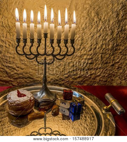 Menorah with the glitter lights of candles, sweet donut and wooden dreidel are traditional Jewish attributes and symbols for Hanukkah holiday. Selective focus. Image toned for retro style