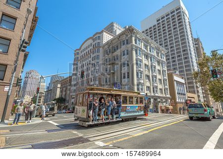 San Francisco, California, United States - August 17, 2016: The popular Cable Car of San Francisco, Powell-Hyde lines, full of tourists along the famous Powell Street while crossing an intersection.