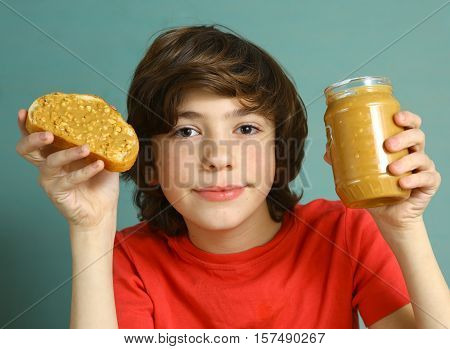 preteen boy hold peanut butter with nut pieces sandwich with jar close up portrait