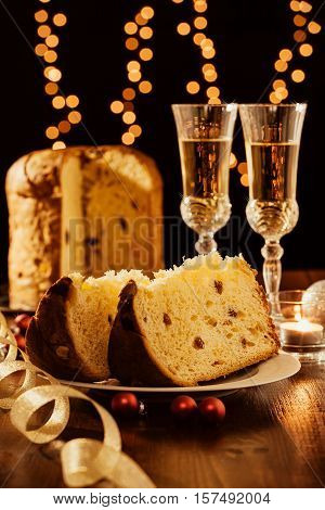 Sliced italian panettone sparkling wine and decorations with Christmas lights on background