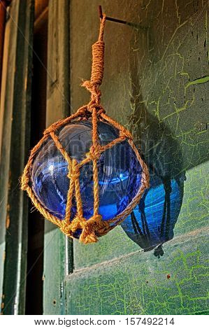 Glass blue buoy on vintage wood door