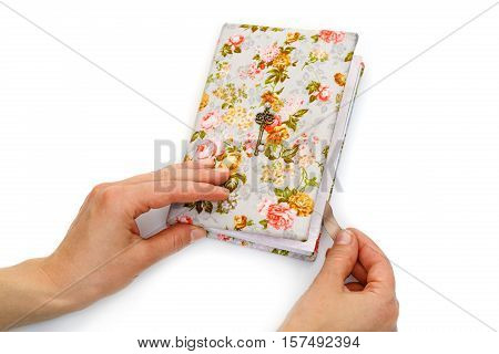Beautiful handmade paper notebook in hard floral cover. Bokmark ribbon with horseshoe pendant detail. Scrapbooking. Female hands opening. Isolated on white. Copy space.