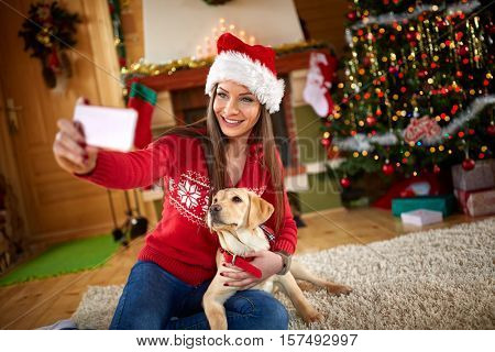 Young girl making selfie with nice puppy on Christmas eve