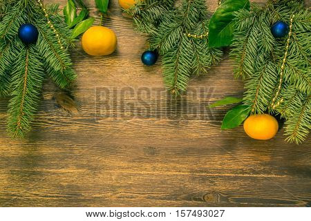 Christmas tree branches with mandarines beads and blue balls