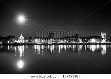 Supermoon rising over Kings Lynn harbour in Norfolk UK. Black and white landscape of building night lights and water reflection light up the harbour after dust
