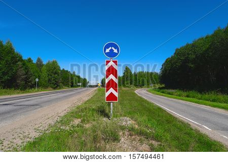 Road sign with arrows. Two different directions. Concept of choose the correct way. Right and left directional traffic signpost. Crossroad sign. Empty highway. Junction fork split road sign post.