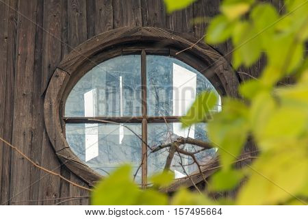 Round attic window in abandoned house with leaves in front