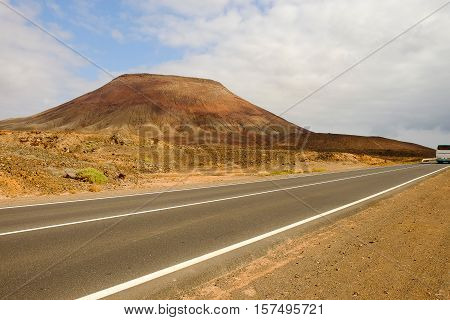 View on a mountain and a road with a bus. Location National Park Corralejo on the Canary island Fuerteventura Spain.