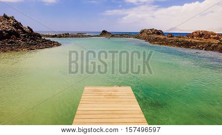 View on a wooden catwalk and lagoon with green water and volanic rocks. Location Canary island Lobos Fuerteventura Spain.