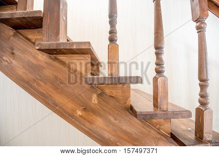 Brown wooden staircase with banister in modern house