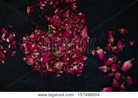 Dried rose petals and buds in a heart shape on a dark background. Romantic ingredient for tea bath or cosmetics. Dark food photography. Horizontal