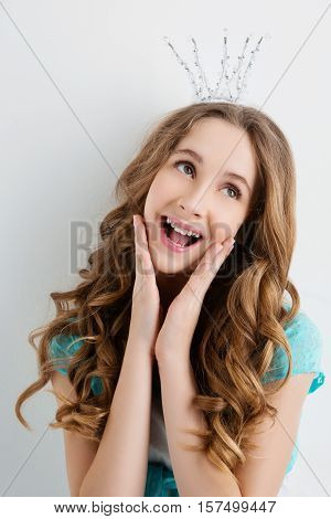 Happy teenage girl with long curly hair and crown on head looking like princess. Surprised expression. Studio portrait on light background. Copy space.