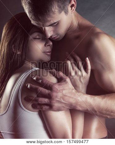 Young beautiful loving couple is embracing on on a dark background
