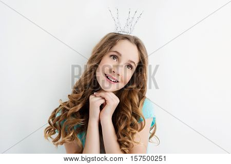 Beautiful teenage girl with long curly hair and crown on head looking like princess. Dreaming expression. Studio portrait on light background. Copy space.