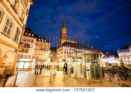 STRASBOURG FRANCE - DEC 24 2015: Christmas MArket stall with people shopping for traditional gifts and food mulled wine in Place Gutenberg