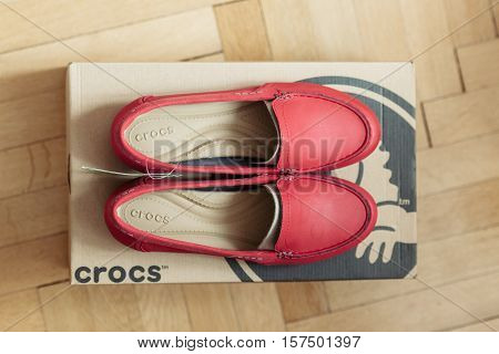 PARIS FRANCE - OCT 182015: Beutiful CROCS shoe placed on cardboard box in luxury retail shopping center with wooden parquet floor