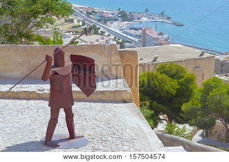 ALICANTE SPAIN - AUGUST 31: figure of a warrior of metal in the castle of santa barbara with the coast in the background. Picture taken on August 31 2016 in Alicante Spain
