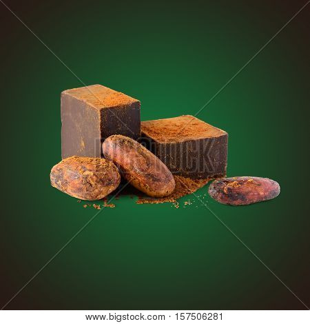 Dark chocolate, cocoa beans and cocoa powder on green background