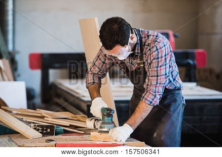 Worker grinds the wood of angular grinding machine.