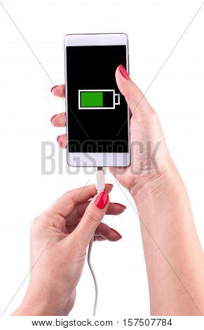 Female hand holding a smartphone and connecting charger, isolated on white background