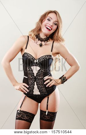 Sexuality concept. Gorgeous attractive smiling girl in black lingerie. Happy alluring woman in corset stockings and suspender belt.