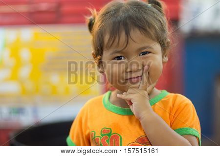 SHIRA THANI, THAILAND, SEPTEMBER 28, 2016 : A shy and mischievous little girl is posing in the night market of Shira Thani, Isaan ,Thailand